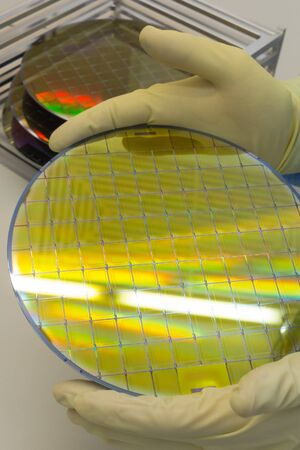Silicon Wafers in steel holder box on table taken out by hand in gloves- A wafer is a thin slice of semiconductor material, such as a crystalline silicon,