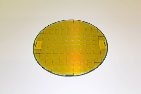 Silicon Wafer with microchip yellow color, backside is grey color - A wafer is a thin slice of semiconductor material, such as a crystalline silicon, .Wafer with microchips.Rainbow on silicon wafer.Color silicon wafers with glare.