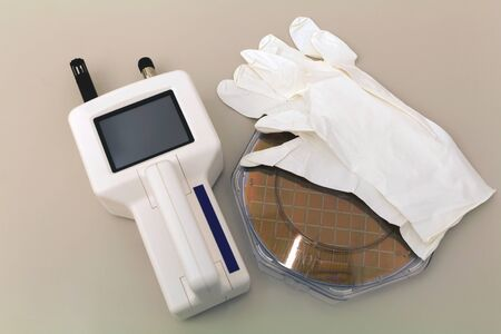 Silicon Wafer in plastic holder box on a table with particle counter and white gloves near in clear room Stock Photo