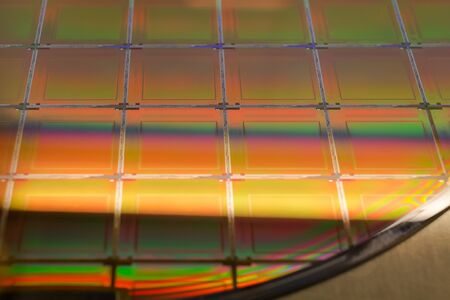 Close up Silicon Wafer with microchips - A wafer is a thin slice of semiconductor material, such as a crystalline silicon, used in electronics for the fabrication of integrated circuits.Several pieces of wafers with microchips.Rainbow on silicon wafers.Color silicon wafers with glare. Stock Photo