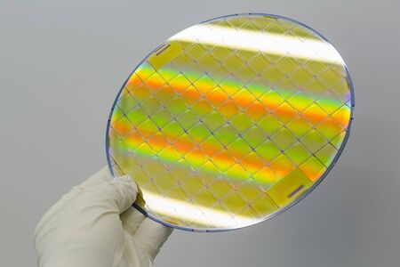 Silicon Wafer with microchips in the hands by gloves - A wafer is a thin slice of semiconductor material, such as a crystalline silicon.Wafer with microchips.Rainbow on silicon wafers.Color silicon wafers with glare.