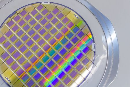 Silicon wafer with microchips fixed in the holder with steel frame on the grey background and ready for process . Silicon Wafers with microchips - used in electronics for the fabrication of integrated circuits.Color silicon wafers with glare.