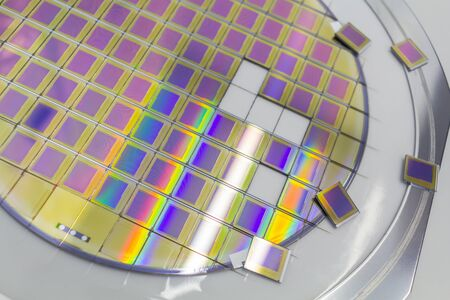 Silicon wafer with microchips fixed in a holder with a steel frame after the dicing process and separate microchips. Silicon Wafers with microchips - used in electronics for the fabrication of integrated circuits.Color silicon wafers with glare. Reklamní fotografie