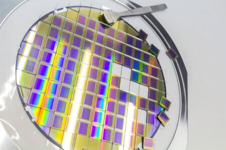 Silicon wafer with microchips, fixed in a holder with a steel frame on a gray background after the process of cutting into cubes. Microchip separation with tweezer. Silicon Wafers with microchips - used in electronics for the fabrication of integrated circuits.Color silicon wafers with glare. Stock Photo
