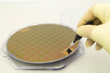 Silicone wafer in a plastic case on the table is take out by hand in a yellow glove and vacuum tweezers on white background .Brown color of silicon wafers.