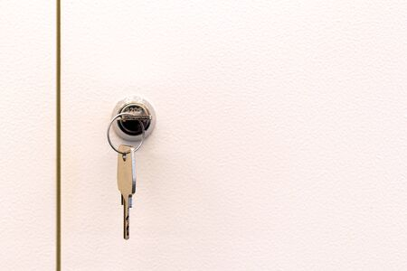 Two plastic white doors of individual box, lock and steel key. Lock and key with soft bright white background.