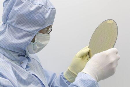 An engineer working in a clear room wearing a special uniform and protective glasses holds silicon wafer with microchips in hand in glove and show it to camera. Stock Photo