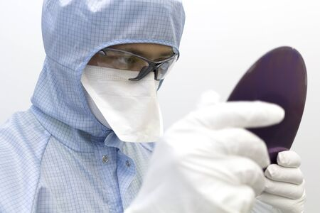 An engineer working in a clear room wearing a special uniform and protective glasses holds silicon wafer with microchips in hands in white gloves and check it.