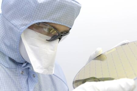 An engineer working in a clear room wearing a special uniform and protective glasses holds silicon wafer with microchips in hands in white gloves and check it. Stock Photo