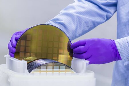 Silicon Wafer with semiconductors in plastic white storage box take out by hand in gloves inside clean room.Wafer with microchips.Rainbow on silicon wafers.Color silicon wafers with glare.
