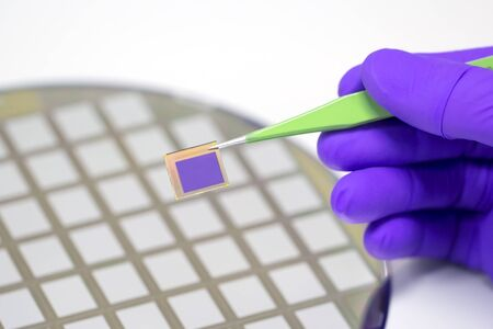 Hand holding microchip with pair of tweezers Silicon wafer with microchips on background.
