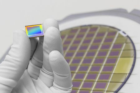 Hand in white glove holding microchip photo sensor matrix . On the background is diced silicon wafer with microchipsFocus on chip.Close up.