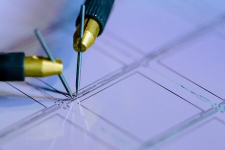 Checking microchips on silicon wafer with probe station.Close up . Semiconductor Crystal Manufacturing.Selective focus.