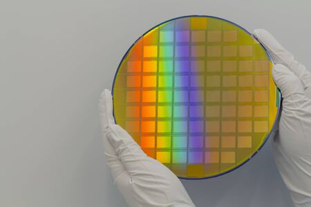 Hands in white gloves holding a silicon wafer with integrated circuits on a white background. Banco de Imagens