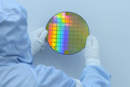 Engineer in clear room in white gloves and suit holding a silicon wafer with integrated circuits on a white background. Reklamní fotografie
