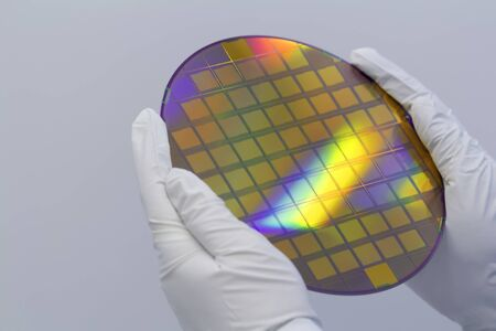 Hands in white gloves holding a silicon wafer with integrated circuits on a white background.