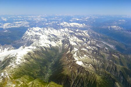 Aerial view of the Alps mountains from the airplane window from above.The view from the airplane window on a picturesque mountains landscape 免版税图像