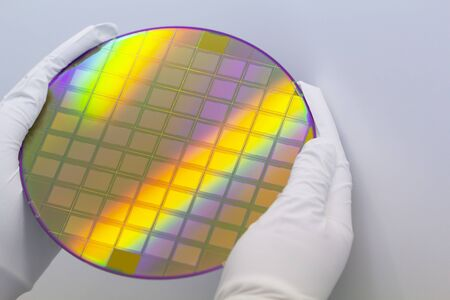 Hands in white gloves holding a silicon wafer with microchips on white background.Banner format.