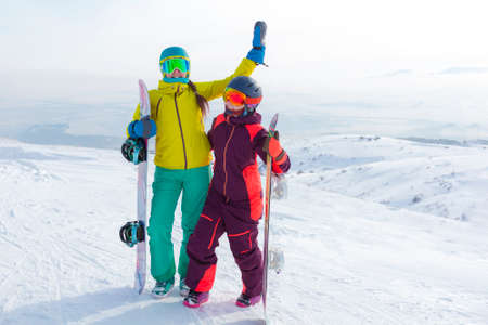 Two girls with snowboards together in snow having fun outside