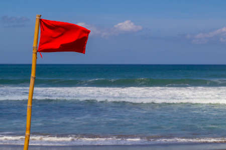 Swimming is dangerous in ocean waves. A red warning flag on the beach in the Nuca Dua Bali, Indonesia. Danger to swim in ocean. Stock Photo