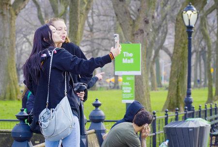 Tourists doing selfies at Central Park New York- MANHATTAN  NEW YORK - APRIL 1, 2017 Editorial