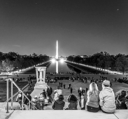 lincoln memorial: People sitting on the steps of Lincoln Memorial in Washington and view over reflecting pool - WASHINGTON DC - COLUMBIA - APRIL 9, 2017