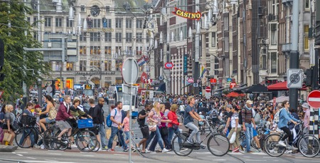 People crossing the street at Damrak in Amsterdam - AMSTERDAM - THE NETHERLANDS - JULY 20, 2017 Editorial