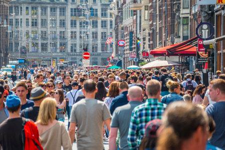 Huge crowd of people at Damrak Street in Amsterdam