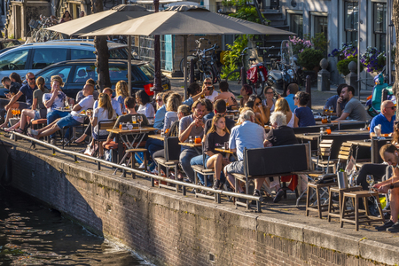 Street cafe at the canals of Amsterdam on a sunny day