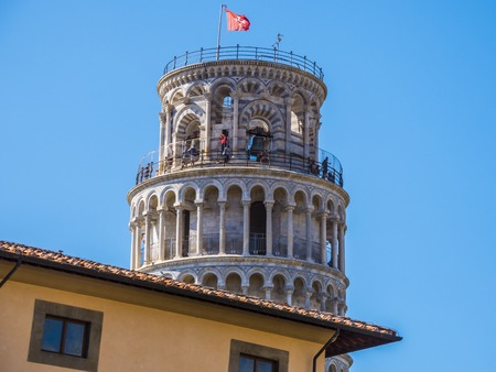 Top of the Leaning Tower in Pisa behind a building - PISA  TUSCANY ITALY - SEPTEMBER 13, 2017 Editorial