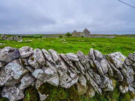 Stone wall and ancient church ruin in Ireland