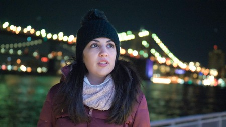 Young woman sits at Brooklyn Bridge New York by night 스톡 콘텐츠