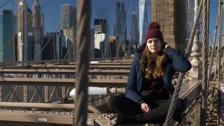 Beautiful girl on Brooklyn Bridge enjoys a sunny day while relaxing