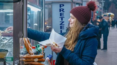 Young woman buys a hot dog in the streets of New York