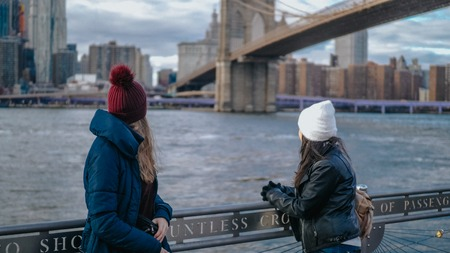 Two girls on a sightseeing tour to New York City at Hudson River