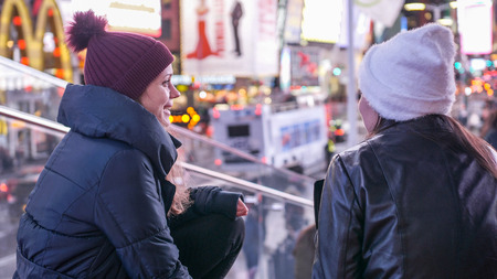 Two girls in New York enjoy the amazing view over Times Square by night - NEW YORK, UNITED STATES - DECEMBER 4, 2018