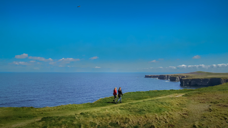 Women walking along Loop Head at County Clare in Ireland - aerial drone footage - travel photography