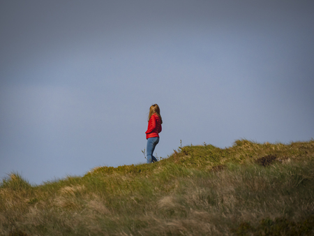 Woman Walk over the infinite grasslands of Binevenagh in Northern Ireland - travel photography Stock Photo