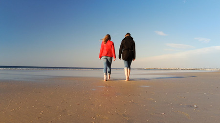 Women Walking along a beach on a chilly day in autumn - travel photography Stock Photo