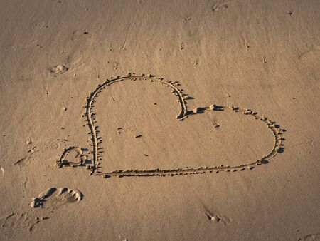 a heart symbol in the sand on a beach - travel photography