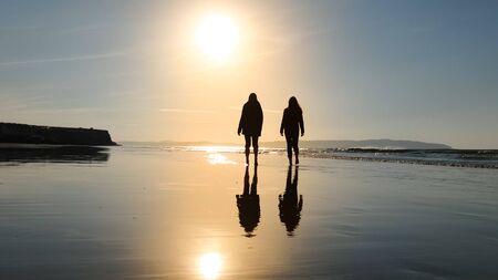 Walking on Castlerock Beach at sunset Stockfoto