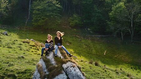 Two girls sit on a rock at Murlough Bay in North Ireland