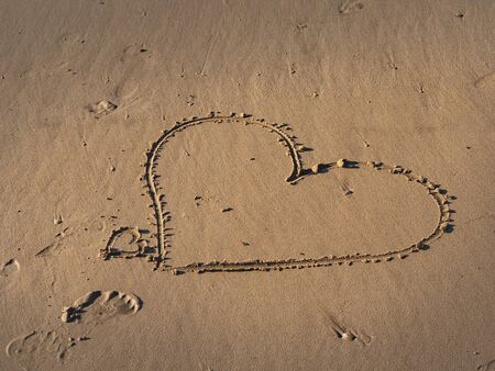 Girl writes a heart symbol in the sand on a beach