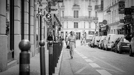 French woman walks through the streets of Paris - PARIS, FRANCE - JULY 29, 2019 Reklamní fotografie
