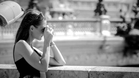 Young woman takes photos on her sightseeing trip to Paris