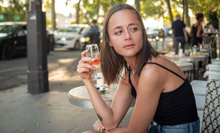 Young woman sits in a street cafe in Paris