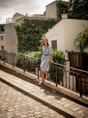French woman relaxes on Montmartre Hill in Paris - PARIS, FRANCE - JULY 29, 2019
