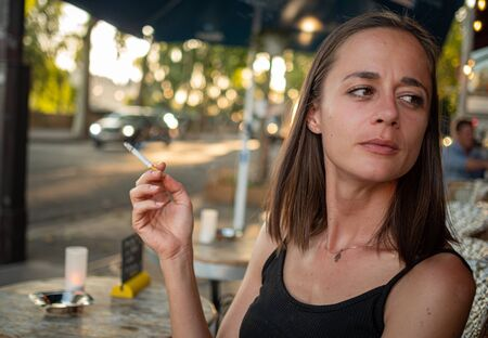 French woman smokes a cigarette in a street cafe in Paris