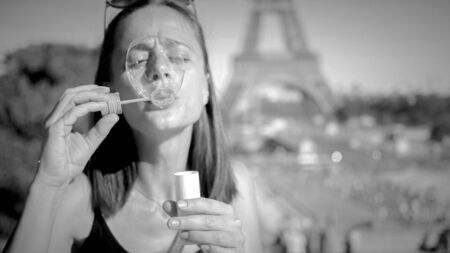Beautiful girl blows soap bubbles in the city of Paris Reklamní fotografie