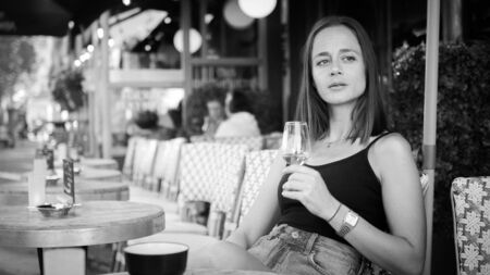 French woman drinks a glass of wine at a street cafe in Paris